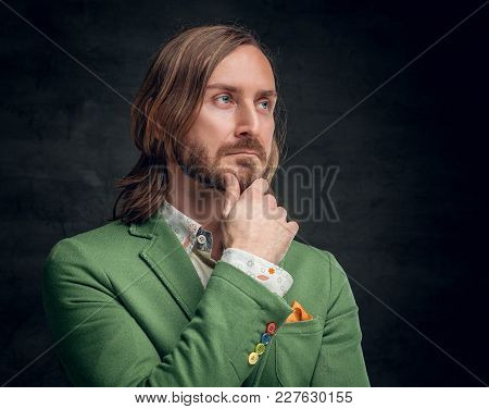 Portrait Of A Stylish Bearded Male With Long Hair Dressed In A Green Jacket.