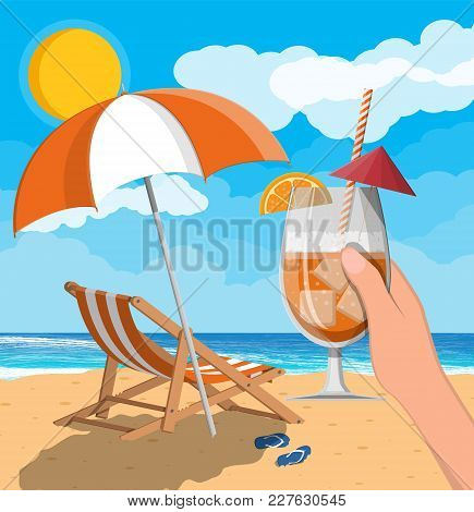 Glass Of Drink Cocktail In Hand. Landscape Of Wooden Chaise Lounge, Umbrella, Flip Flops On Beach. S