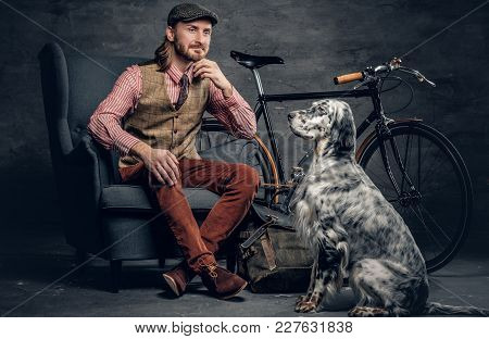 A Stylish Bearded Man In A Cap Sits On A Chair With An Ireland Setter Dog And A Bicycle On A Backgro