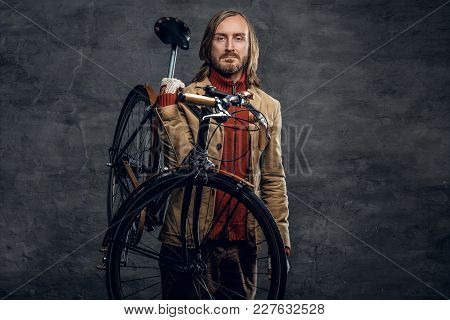 Stylish Bearded Male With Long Hair Holds Single Speed Bicycle On His Shoulder Over Grey Background.