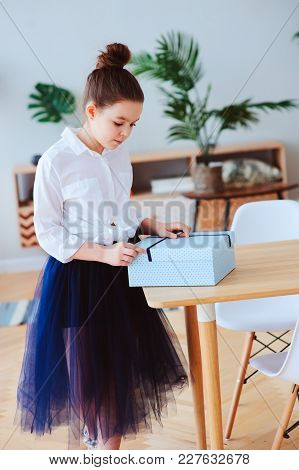 Happy Kid Girl With Gift For Birthday Or Womans Day Posing At Home In Modern Scandinavian Interior,