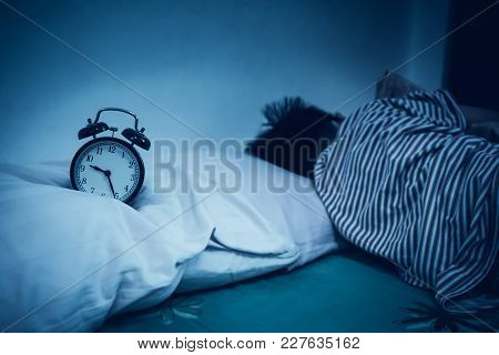 Antique Black Alarm Clock In Front Of Asian Boy Sleeping On Bed In Dark Bedroom At Home. Child Relax