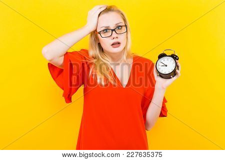 Portrait Of Attractive Surprised Blonde Woman In Glasses And Red Dress Isolated On Yellow Background