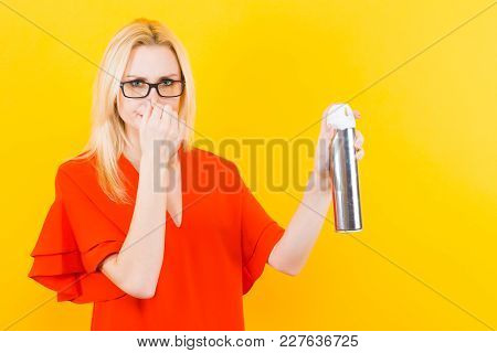 Portrait Of Attractive Blonde Woman In Red Dress And Glasses Isolated On Yellow Background Holding A