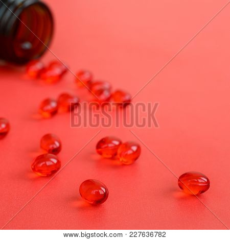 A Lot Of Transparent Red Tablets Were Scattered From A Small Glass Brown Jar On A Red Surface