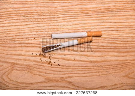 Two Cigarettes, One Broken, On Surface Of Wooden Table