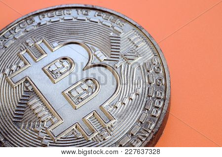 Chocolate Product In The Form Of Physical Bitcoin Lies On An Orange Plastic Background. Model Of The