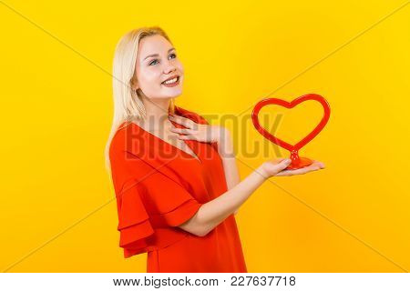 Portrait Of Attractive Pleased Woman In Red Dress On Yellow Background With Copyspace Holding Plasti
