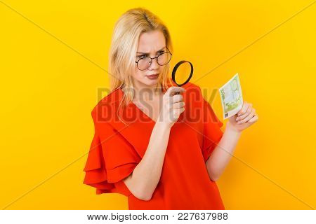 Portrait Of Attractive Blonde Woman In Red Dress And Eyeglasses Isolated On Yellow Background Lookin