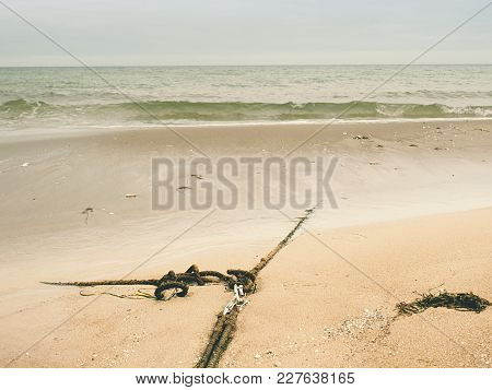 Ship Old Anchor Rope With Snap Hook And Line Under Sea. Steel Shackle Hidden In Sand