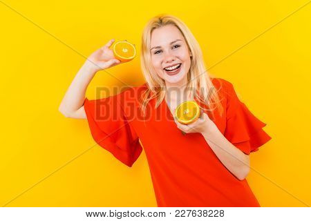 Portrait Of Attractive Smiling Woman In Red Dress Isolated On Yellow Background Holding Two Halfs Of