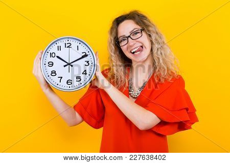 Portrait Of Attractive Curly-haired Woman In Red Dress And Eyeglasses Isolated On Orange Background