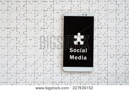 A Modern Big Smartphone With A Touch Screen Lies On A White Jigsaw Puzzle In An Assembled State With