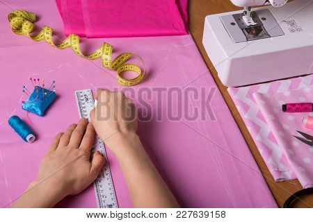 Hands Seamstress Cut Fabric On The Desktop, Near Sewing Accessories And Sewing Machine