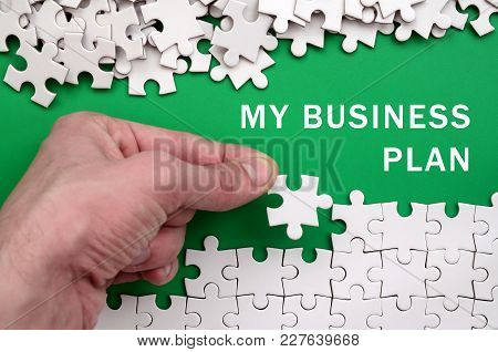 My Business Plan. The Hand Folds A White Jigsaw Puzzle And A Pile Of Uncombed Puzzle Pieces Lies Aga