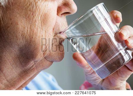 Side view of elderly woman drinking water