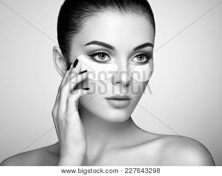 Portrait Of Beauty Woman With Eye Patches Showing An Effect Of Perfect Skin. Beautiful Face Of Young