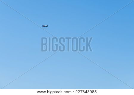 Red-and-white Plane Flying Through The Sky To Land. Plane In The Cloudless Blue Sky.