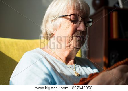 Senior woman knitting for hobby at home