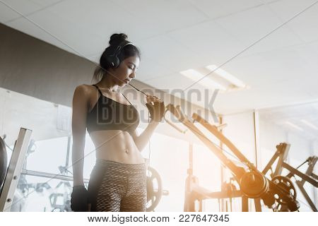 Asian Woman Wearing Headphones For Listening Music At Gym.