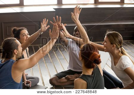 Mindful Happy Sporty Diverse People Join Hands Together At Group Seminar Sitting On Mats In Studio,