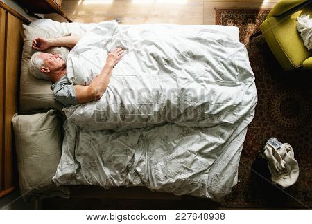 Elderly Caucasian man sleeping on the bed