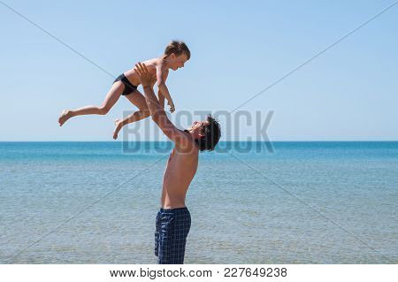 Young Happy Father Holding Up In His Arms Little Son Putting Him Up At The Beach, Having Fun With Th