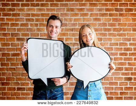 Happy cute young couple holding an empty placard thought bubble copyspace
