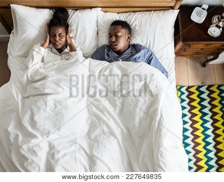 African American couple on bed, man snoring and disrupting woman's sleep