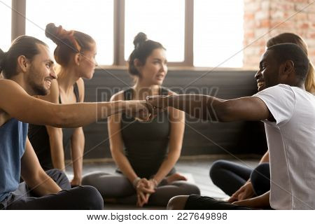 Smiling Sporty Fit African American And Caucasian Men Fist Bumping At Group Training Meeting In Gym