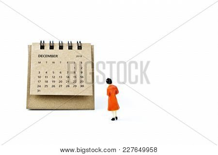 December. Two Thousand Eighteen Year Calendar And Miniature Plastic Woman On White Background.