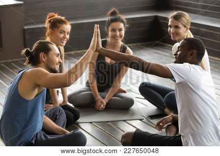 Smiling Diverse Yoga Team Members Giving High Five At Group Class, Fit Sporty Young African And Cauc