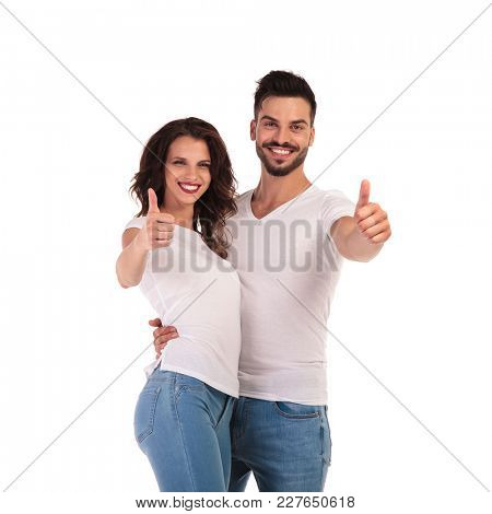 happy young casual couple making ok sign on white background