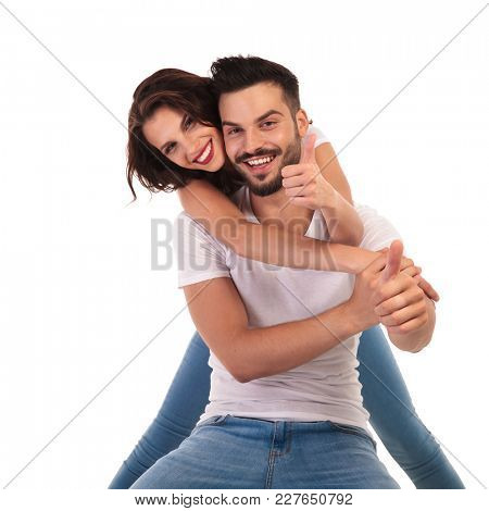 happy young couple making ok sign together on white background