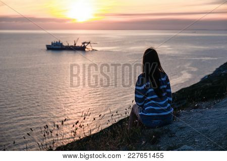 Unrecognizable Woman In Striped Sweater Admires The Sunset On Mountain With Seascape View Back View