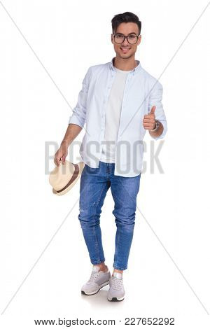 happy casual man holding hat making the ok thumbs up hand gesture on white background