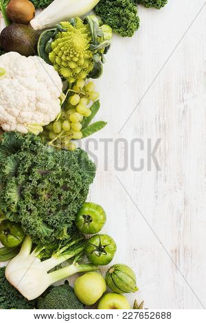 Green Vegetables And Fruits On The White Wooden Table, Copy Space For Text On The Left, Verical, Top