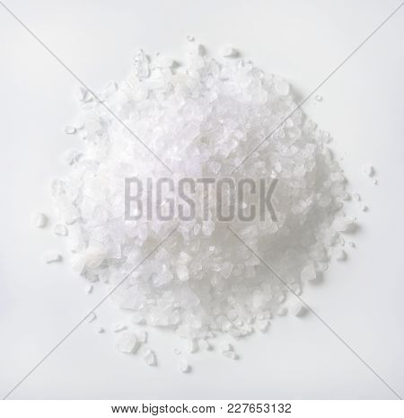 pile of coarse grained sea salt on white background