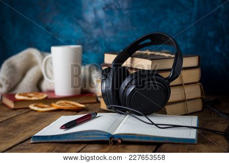 Books Are Stacked, Headphones, White Cup, Orange Slices, Open Diary On A Wooden Background. The Conc