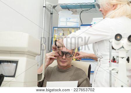 Woman Optometrist Checks Vision For A Mature Man