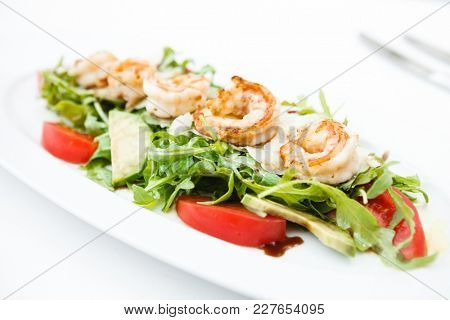 Rocket salad with fried shrimps and avocado