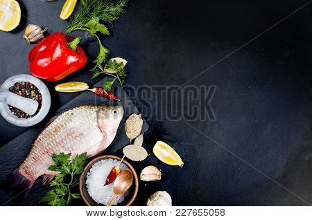 Raw Crucian, Herbs And Spices For Cooking Fish On Black Table. Parsley, Dill, Lemon Pepper And Salt.