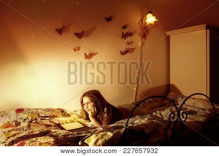 Little Caucasian Girl Reading A E-book In The Bed. Children, Immagination And Modern Tecnology Conce