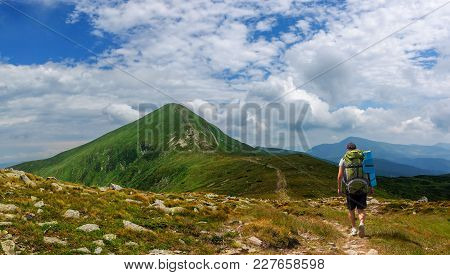 A Tourist With A Large Backpack Rises To The Highest Mountain In Ukraine - The Goverla Mountain In C