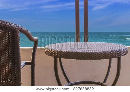 Brown Rattan Desk And Chair On Balcony Inside Sea View Of Hotel Room