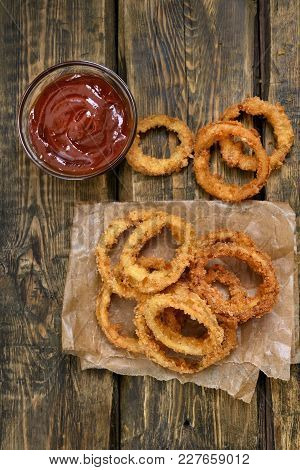 Onion Rings With Tomato Sauce On Wooden Background. Top View, Flat Lay