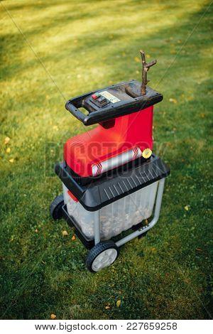 garden chipper, electric shredder (mulcher), green grass background