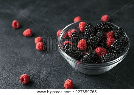 Glass Plate With Ripe Red Blackberries And Raspberries On A Black Surface.