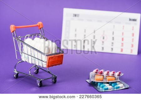 Tampons In Small Shopping Cart, Pills And Calendar On Purple