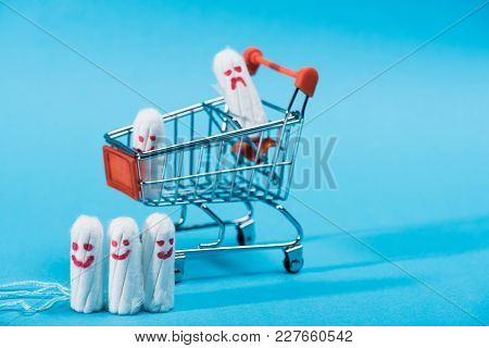 Tampons With Happy And Sad Smileys In Small Shopping Cart On Blue